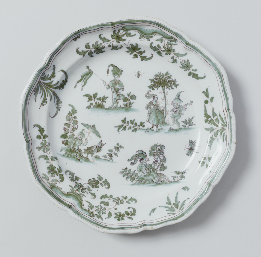 Circular plate with scalloped edge; dark green decoration with foliage design around edge, scene with figure in center.