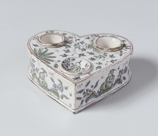Heart-shaped inkstand (a) with two cylindrical containers (b,c) at top left and right, and circular depression at bottom center; green foliage decoration throughout, figure in depression near point.