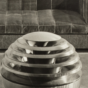 The present black and white photograph features a prototype of Gustav Jensen's patented design for a table-top radio cabinet, here positioned on a round glass table resting on a carpet. In the background is a furniture unit composed of a sofa-with-attached-end-tables fabricated of a hard-surfaced material, perhaps marble or plastic, and a seat cushion and arm rests, apparently of tufted velvet.  The featured object, a round radio cabinet on a cylindrical pedestal, has five ziggurat levels, beginning about midway and diminishing in size from there to the top; the sound is emitted through the openings. The tuning dial is located on the base. The carpet, visible through the table top and beyond, features a design of swirling flowers in a lighter tone than the background.