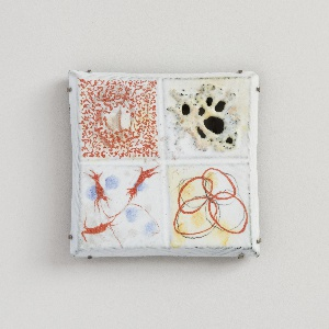 Square brooch consisting of quadrants with abstract enamel decoration in white, red, blue and yellow; top right quadrant pierced.