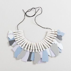 Series of small clothespins strung on cord, each holding a torn fragment of a colorcore sample in tones of gray, blue, and violet.