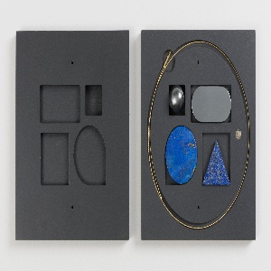Flexible gold wire necklace with four interchangeable geometric pendants: lapis disc and triangle, hematite ball and lozenge. Two-piece square container with shaped cavities for necklace and pendants.