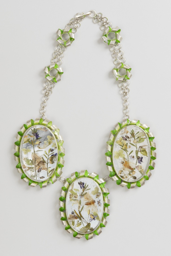Necklace with three large oval pendants containing floral designs; each surrounded by a coiled green and silver border; chain of large links and clasp.