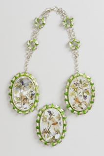 Necklace with three large oval pendants containing floral designs; each surrounded by a coiled green and silver border; chain of large links and clasp. *Green pigment not consistently applied