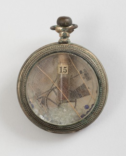 Brooch consisting of green-patinated circular pocket watch case containing engraved diagram and found objects. Reverse covered by fragment of a printed page of text with a small, faceted lozenge-shaped purple glass paste adhered under bar pin.