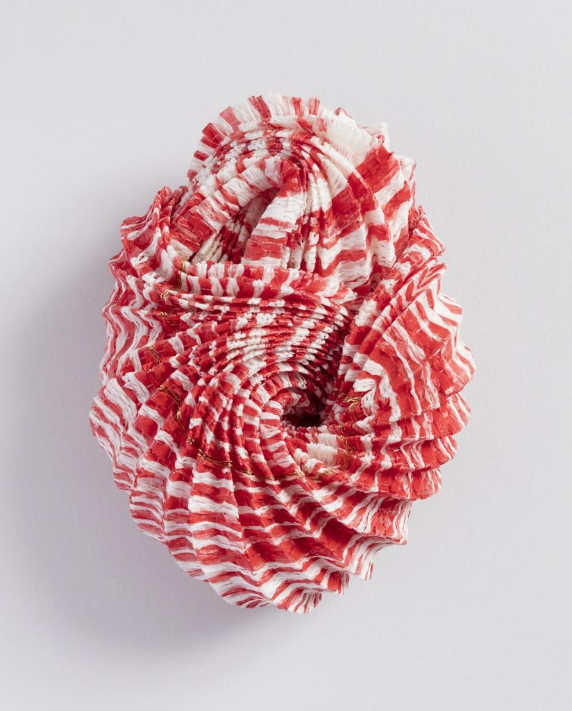 Ovoid form of creased red and white paper suggestive of a seashell or plant form.
