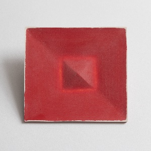 Brooch in form of two concentric squares in tones of red with white at edges.