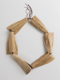 Flexiblel necklace composed of six triangular, contoured wooden elements strung on brown cord.