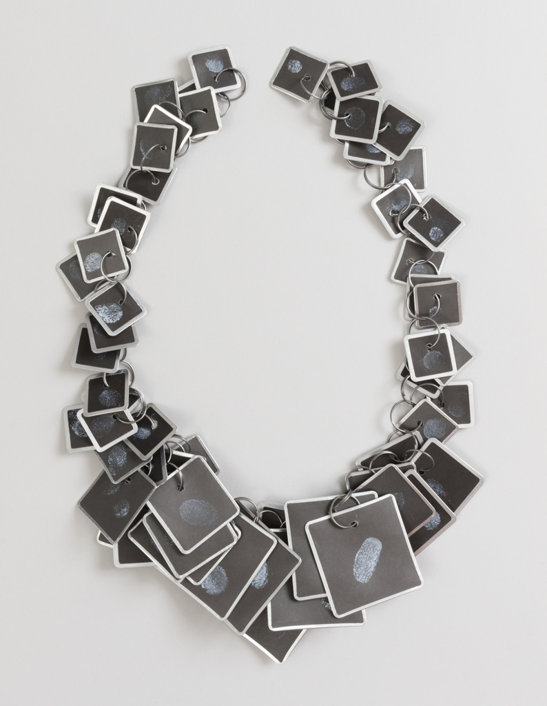 Flexible necklace consisting of linked key tags in graduated sizes, imprinted with the artist's fingerprints; 100 prints - 10 of each finger.