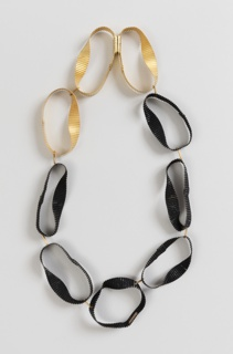 Necklace composed of irregular and enameled thin gold loops rippled to resemble corregated cardboard.