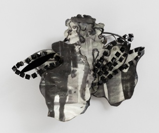 Flower-form brooch in black and tones of gray, with photographic image on petals.