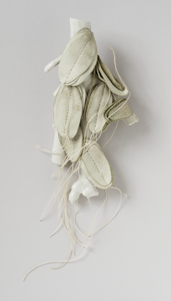 White porcelain and twig, Porcelain cast as coral with leather leaves mounted on front, attached with glue and string