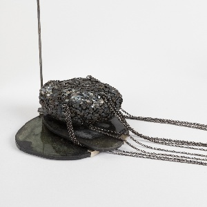 Large pendant reminicent of a head, covered with black nails and panels, wrapped in chain loops; tall wire stand with base composed of two  irregular polished discs.