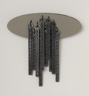 Flat, dark gray oval form with array of perforated rods hanging from center.