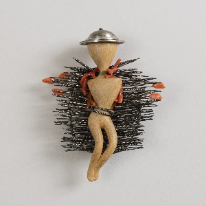 Abstract wooden figure wearing cap, surrounded by numerous wire-wrapped projections and coral bits; housed in rectangular gray paper box.