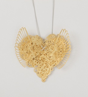 Heart shaped necklace resembling clockwork, key, box and tag.