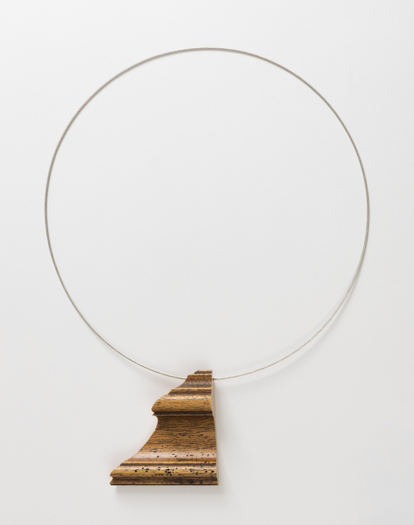 Hoop necklace with a roughly triangular pendant made from a fragment of wood molding.