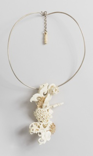 Intricate pendant of carved and assembled animal, floral, and scrolling forms and two wheels that turn (containing diamonds), depending from wire loop necklace; short chain with simple bone pendant at closure.