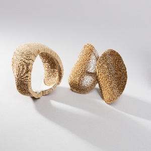 Contoured, currogated cardboard cuff type bracelet, the openwork surface backed by silver frame.