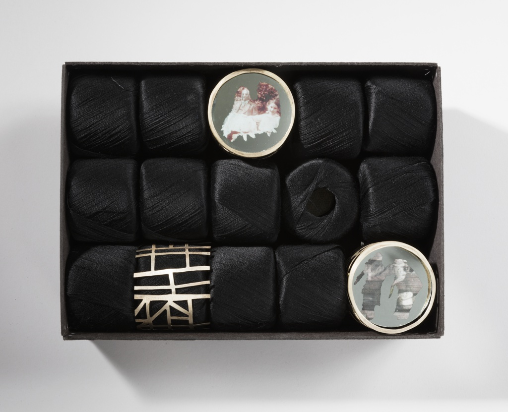 One cylindrical open-work metal brooch and two circular brooches with photographic images housed in a black rectangular box with fifteen skeins of black thread.