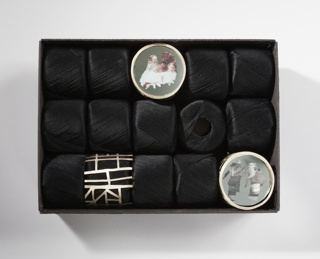Three brooches housed in box with 15 skeins of black thread.