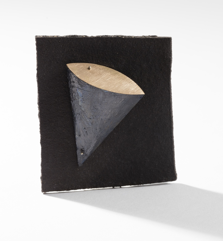 Flattened cone with black, textured, curved surface and gold flat edge, mounted on roughly rectangular sheet of textured, matt-black stoneware; a tiny gold ball near vertex and one on flat edge. Bar pin closure on back.
