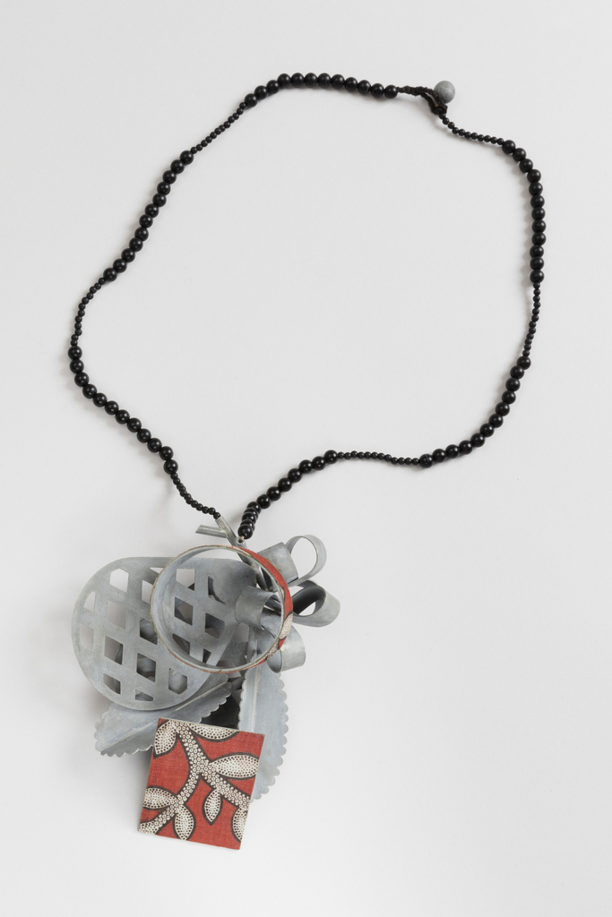Pineapple shaped Zinc focal point at center of necklace.