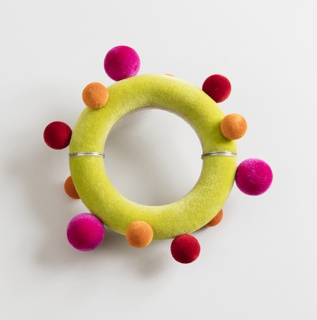 Green circular bracelet with red, orange, and pink spherical protrusions of varied sizes.