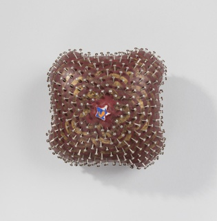 Roughly square pincushion-form brooch covered with inserted straight pins radiating from center star-shaped decoration in white, orange and blue; all on mottled red and gold-painted ground.