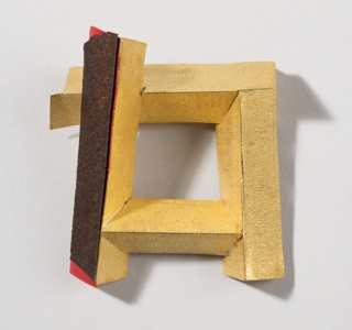 Textured gold brooch of interlocking segments composing an open square; one side lacquered black and orange.