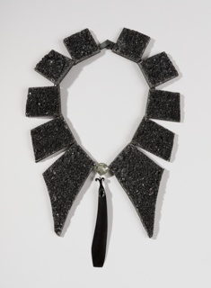 Black necklace composed of an oblong pendant flanked by a series of flat trapezoidal forms in graduated sizes.