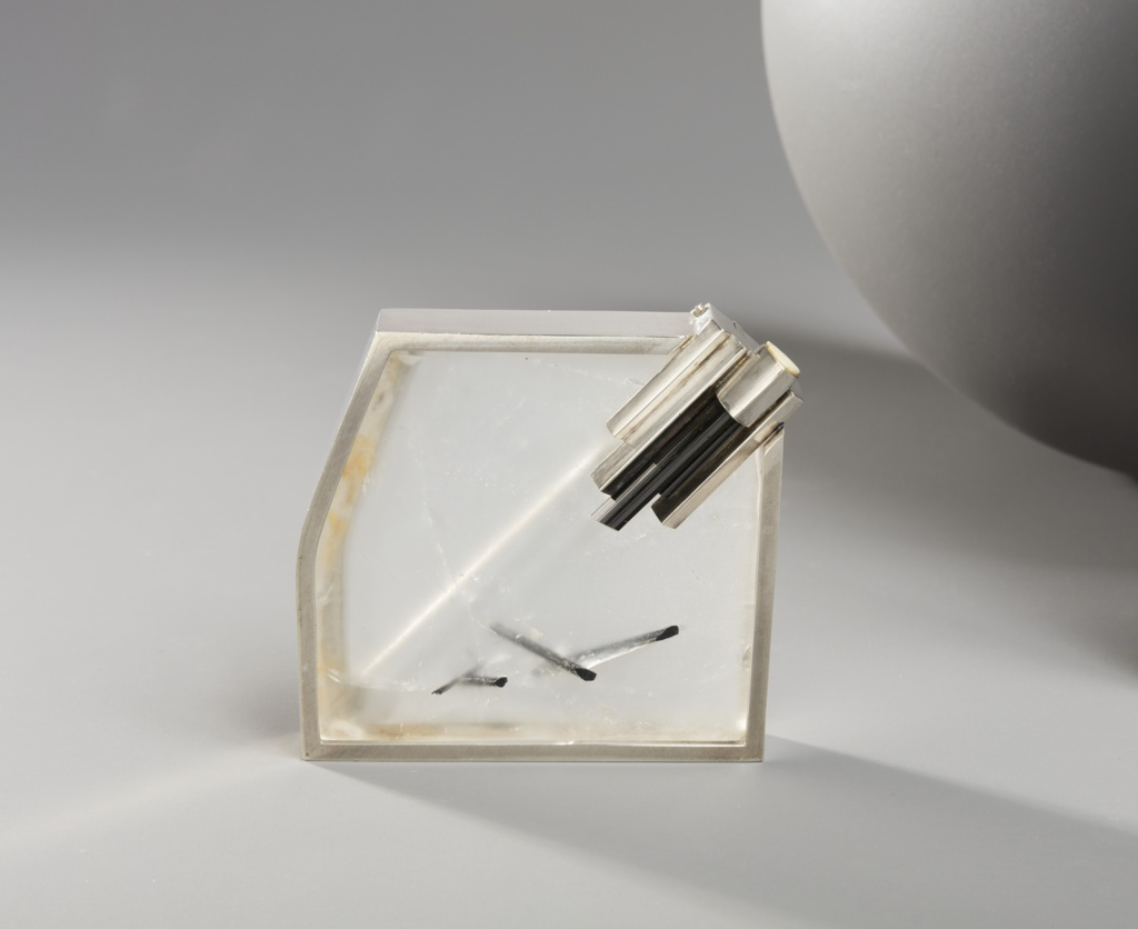 Rectilinear form of silver-framed quartz with black inclusions.