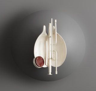 White concave brooch containing spindly segments and a red circular accent.