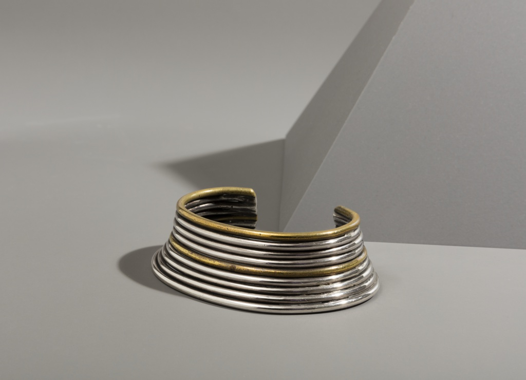 C-shaped bracelet composed of alternating bands of brass and silver