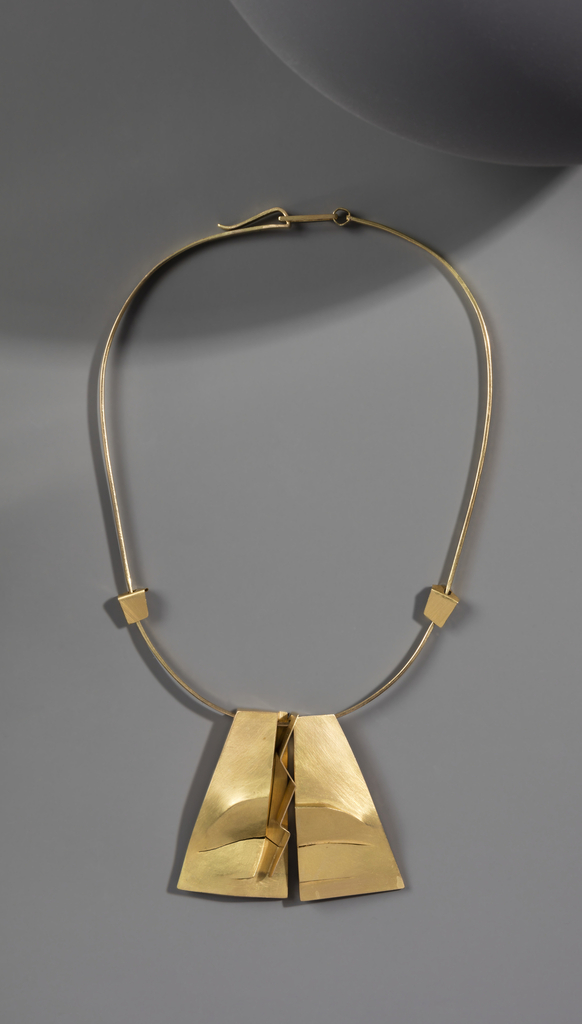 Gold necklace with two hanging pendants depicting two sides of a mouth split down the middle, a third zig-zag shaped pendant between them.