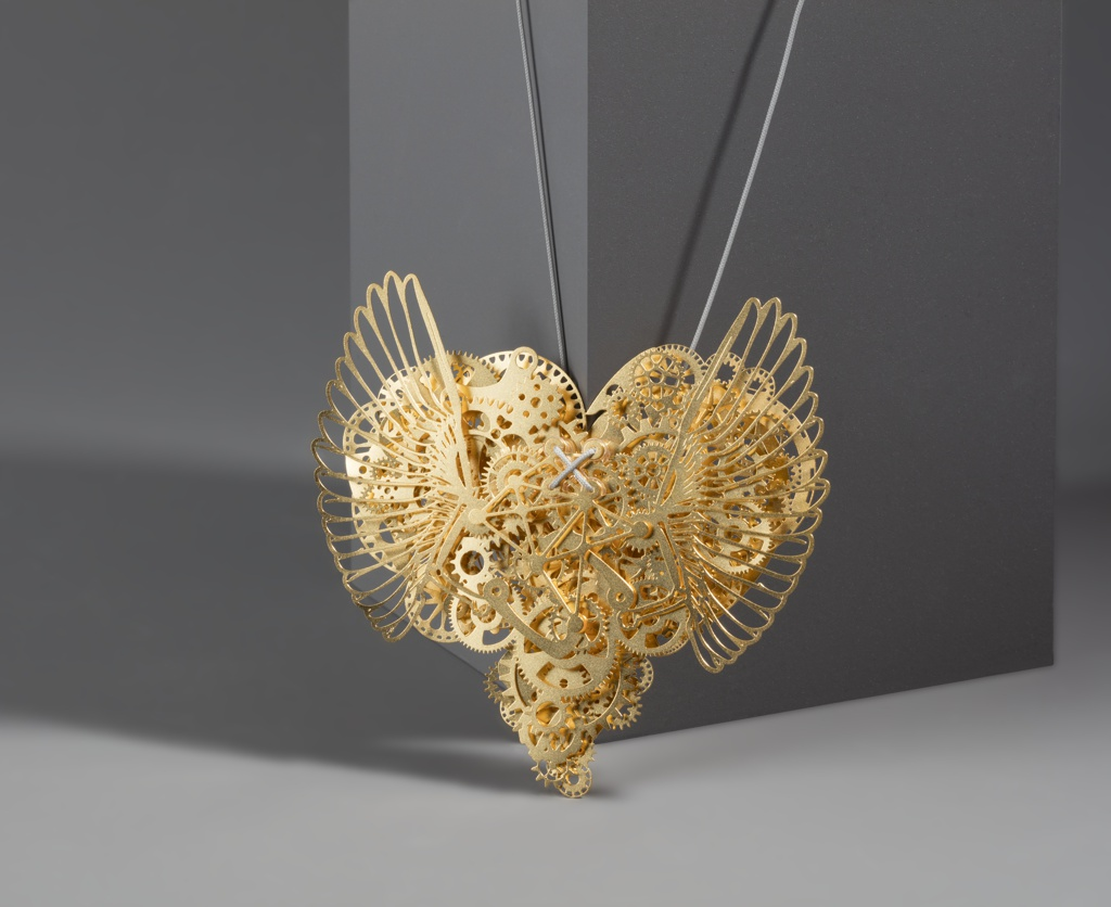 Heart shaped necklace resembling clockwork (a); separate miniature key (b); separate tag (c). Rectangular wooden storage box (d).