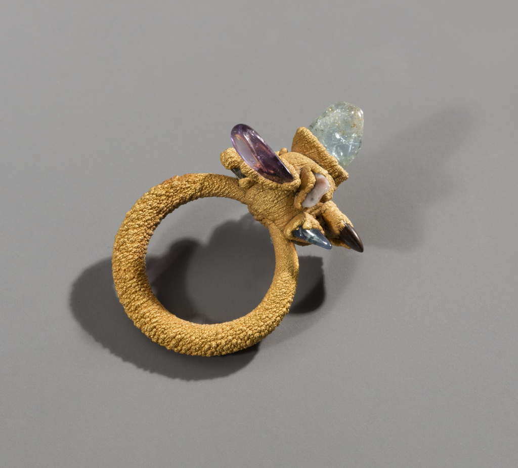 Circular ring with globular projection containing irregularly shaped prism-like stones of different colors.