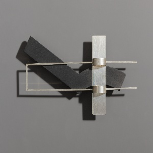 Construction of overlapping flat silver and black slate geometric forms.