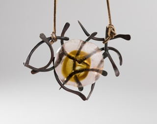 Lanyard tied to Pendant of amber-colored circular glass mass in irregular curvilinear copper cagework.