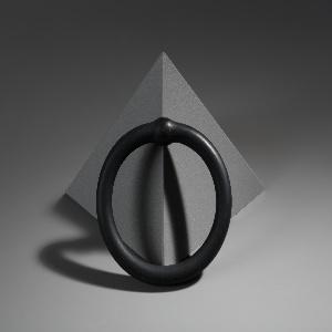 Circular black bangle bracelet with globular segment (black rubber sleeve over gold).