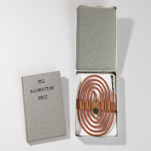 Flexible thin tube and apparatus for exhaling smoke. Tube, apparatus and instruction book housed in metal clamshell box hinged at top.