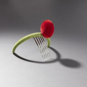 Green-flocked tiara in form of band with large red-flocked spherical accent; five long teeth protruding from underside to secure in wearer's hair.