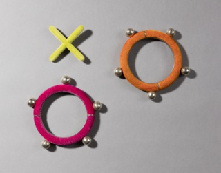 X-form sterling silver brooch covered in chartruse flocking (a); two circular sterling silver bracelets, one covered in pink flocking (b) and one covered in orange flocking (c), with silver spheres distributed along their surfaces.