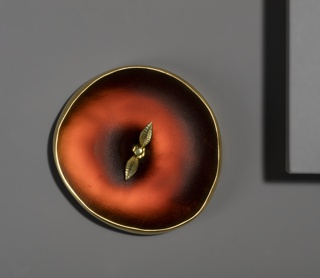 """Roughly circular red glass form resembling an apple seen from above, with gold edge and two gold leaves and """"stem"""" in center."""