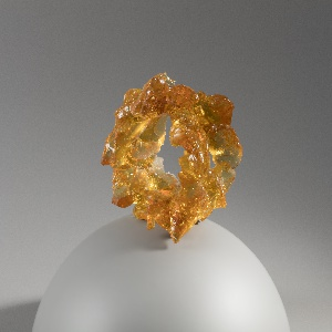 Flexible amber-colored resin cuff bracelet with irregular surface, resembling solidified textured gel.