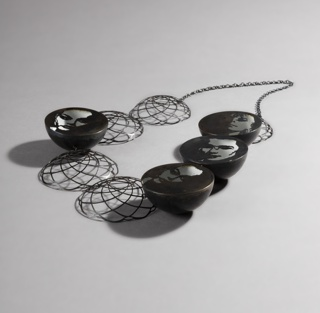 Nine steel discs, four with portrait images, five with curvilinear openwork decoration, with fine-link chain.