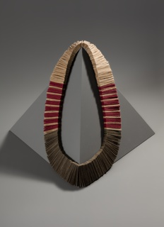 Handmade small rectangular thick paper strips in red and two tones of brown, strung together to form flexible necklace.