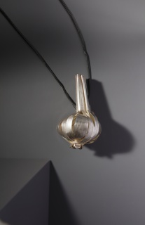 Silver pendant in shape of garlic bulb on long cord.