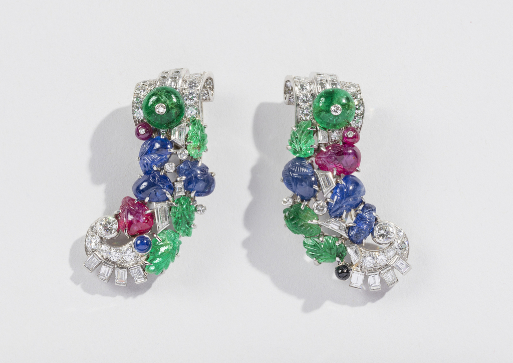 Asymmetrical pair of earrings in the shape of curving swags comprised of carved emeralds, sapphires, and rubies terminated in scrolling diamond volutes on either end, while geometric gems and cabochons irregularly punctuate both pieces.