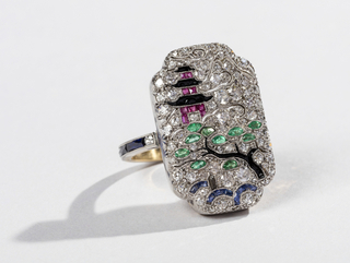 Emerald-shaped ring with inverted corners; a japonesque scene with pagoda, cantilevered tree and stream are articulated by inset diamonds, rubies, emeralds, sapphires and onyx. Gold band accented by sapphire baguettes and diamonds.
